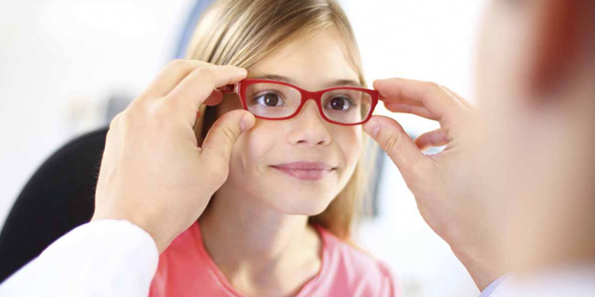 Young girl trying on new glasses